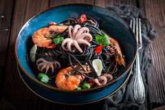 Tasty seafood black pasta made of octopus, tiger prawns Stock Photo