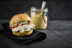 Tasty seafood burger with pollock fish. Tasty seafood burger with a grilled or baked pollock fish fillet and fresh salad trimmings on a crusty bun served with a stock images