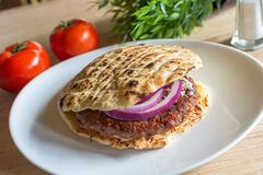 Tasty Serbian hamburger in pita bread with fresh salad ingredients. Hamburger made in Serbia in pita bread with fresh salad ingredients Stock Photos