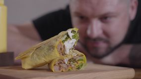 Tasty shawarma with sauce lying on the wooden board close-up. Blurred face of a hungry man looking at the shaurma in the. Tasty shawarma with sauce on it lying stock video