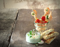 Tasty shrimp appetizers. Tasty prawn or shrimp appetizers with tomatoes on skewers served with tartare sauce and fresh oven-baked Italian focaccia bread on an Royalty Free Stock Photo