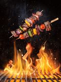Tasty skewers flying above cast iron grate with fire flames. Freeze motion barbecue concept royalty free stock photo