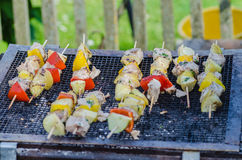 Tasty skewers of fresh fish with vegetables and apples on a wooden shish kebab Stock Image