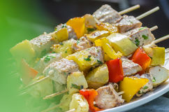 Tasty skewers of fresh fish with vegetables and apples on a wooden shish kebab Stock Photo