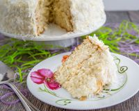 Sliced Coconut Cake for Easter. Tasty slice of coconut cake on wood background and flower plate for Easter Royalty Free Stock Images