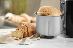 Tasty sliced loaf from bread machine. On table Stock Photography