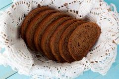 Tasty sliced rye bread in basket. Tasty sliced rye bread on white lace napkin in basket Stock Images