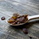 Tasty Small Black Raisins On A Wooden Spoon Royalty Free Stock Photos