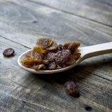 Tasty small black raisins on a wooden spoon. Close up Royalty Free Stock Photos