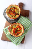 Tasty small individual pumpkin quiches. In crispy pastry cases with a custard base and herbs on a cutting board and napkin for a tasty autumn meal or appetizer royalty free stock photography