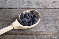 Tasty small raisins on wooden spoon Royalty Free Stock Image