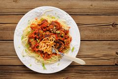 Tasty spaghetti with meatballs in tomato sause on wooden table o Stock Photography