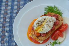 Tasty, spiced poached egg and sandwich on blue napkin. Tasty, spiced poached egg and sandwich, decorated with tomato, cheese, soy sauce on white plate Royalty Free Stock Photos