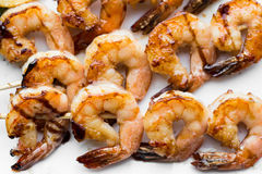 Tasty spiced shrimp skewers on a barbecue.  Stock Photos