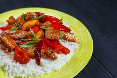 Tasty spicy stir-fry chicken with rice and roasted vegetables in royalty free stock images