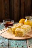 Tasty square layered lemon cake with black tea and lemon curd on Royalty Free Stock Image
