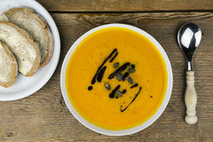 Tasty starter to an autumn meal with creamy soup. Tasty starter to an autumn meal with creamy pumpkin or butternut soup served in a bowl and garnished with seeds royalty free stock photos