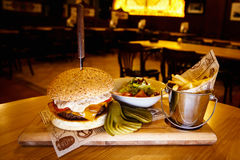 Tasty Steak Burger with Ham Slices on a Wooden Bar fries and vegetables Stock Photos