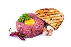 Tasty Steak tartare. Classic steak tartare over white. Ingredients: Raw beef meat salt pepper egg garlic chili herb decoration and Stock Image