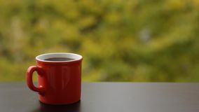 Tasty steaming hot coffee in red cup, cafe table outdoors. Autumn background stock video footage