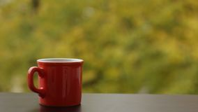 Tasty steaming hot coffee in red cup, wooden cafe table outdoors. Autumn background stock video footage