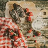 Tasty strawberries, milk and sweet patties on a table. Strawberry, fresh milk and sweet patties on a brown wood table Stock Images