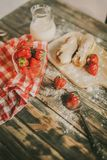 Tasty strawberries, milk and sweet patties on a table. Strawberry, fresh milk and sweet patties on a brown wood table Royalty Free Stock Image