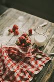 Tasty strawberries and milk on a table. Strawberry and milk on a brown wood table Stock Image