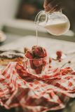 Tasty strawberries and milk on a table. Strawberry, fresh milk and sweet patties on a brown wood table Royalty Free Stock Photography