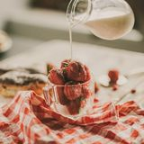 Tasty strawberries and milk on a table. Strawberry, fresh milk and sweet patties on a brown wood table Stock Images