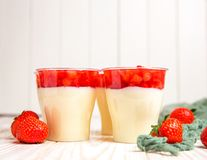 Tasty strawberry mousse pudding or panna cota. Tasty red strawberry mousse pudding or panna cota in glass on white wooden table Royalty Free Stock Images