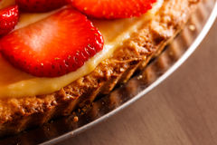 Tasty strawberry tart placed on wooden table Royalty Free Stock Image