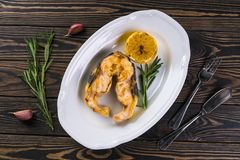 Tasty sturgeon grilled steak. Served fish with lemon and rosemary. On rustic wooden table Stock Image