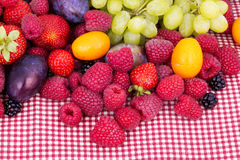 Tasty summer fruits on a red tablecloth Stock Photography