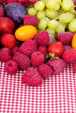 Tasty summer fruits on a red tablecloth Royalty Free Stock Photo