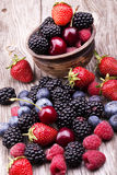 Tasty summer fruits on a wooden table. Cherry, Blue berries, strawberry, raspberries, Blackberries, pomegranate royalty free stock image