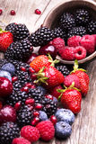 Tasty summer fruits on a wooden table. Cherry, Blue berries, strawberry, raspberries, Blackberries, pomegranate royalty free stock images