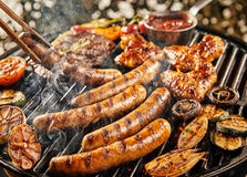 Tasty summer picnic with grilling food on a BBQ. Tasty summer picnic with grilling food sizzling over the hot coals on a BBQ including steak, sausages, chicken Stock Photography