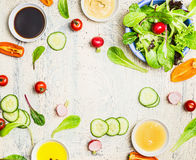 Tasty summer salad and dressing preparation on light rustic background, top view, frame. Healthy lifestyle Royalty Free Stock Images