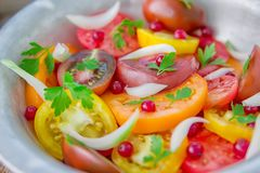 Tasty summer salad of sliced fresh colorful tomatoes, chopped red onion with white currant berries, olive oil, and parsley. Healt. Hy meal royalty free stock images