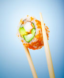 Tasty sushi roll. With crab, cucumber, avocado and red caviar in chopsticks isolated on blue background, traditional japanese food Royalty Free Stock Images