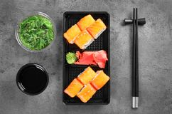 Tasty sushi rolls served on grey table, top view. Food delivery royalty free stock images
