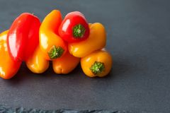 Tasty sweet bell peppers on black stone. Bright red yellow orange vegetables royalty free stock image