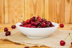 Tasty sweet cherry on wooden background.  royalty free stock image