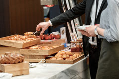 Tasty and sweet croissants at the buffet. Cannot resist their gorgeous smell. Cropped view of a couple in official attire standing by the buffet table and taking Royalty Free Stock Photo