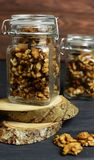 Tasty sweet and healthy snacks walnuts in a glass. Jar delicious sweet and healthy snacks walnuts in a glass jar on wooden sawn logs Royalty Free Stock Photo