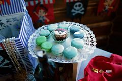 Tasty sweet homemade macaroni cookies, pirate style, white lace dish with blue sweets, execution buffet for children`s birthday.  stock photo