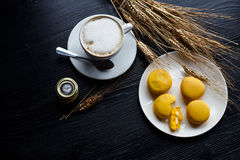 Tasty sweet macarons and coffee cup. Macaroons on black background. Top view. Royalty Free Stock Photography