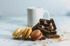 Tasty sweet macarons with cup of coffee on background stock image