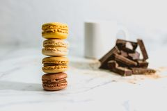 Tasty sweet macarons with cup of coffee on background royalty free stock photography